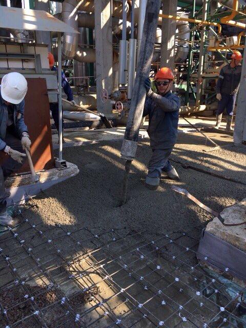Рабочие заливают бетон армированный сеткой базис